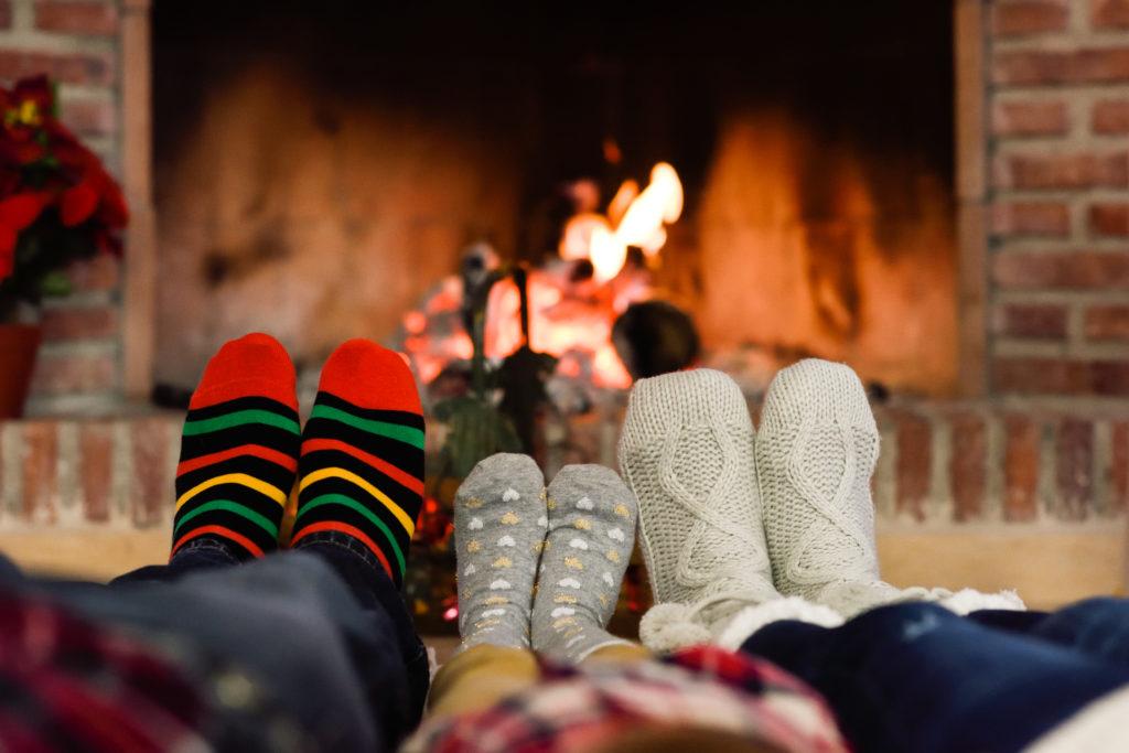 pies de familia delante de la chimenea, felices sin humedad