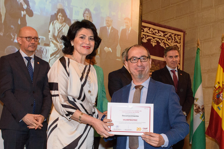 Momento en el que Juan Federico Gallardo recoge el reconocimiento de manos de Mercedes Romero, Presidenta del CAF Córdoba.