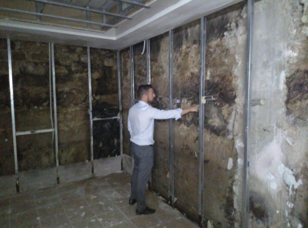 Manuel Martínez comprobando los muros del sótano afectados con humedades por filtración lateral