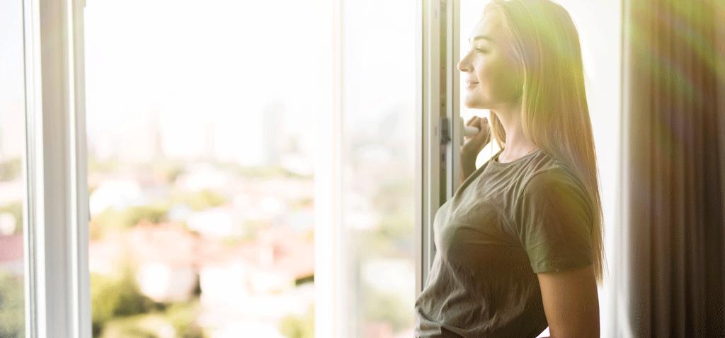 Mujer abriendo ventana para mejorar la calidad del aire