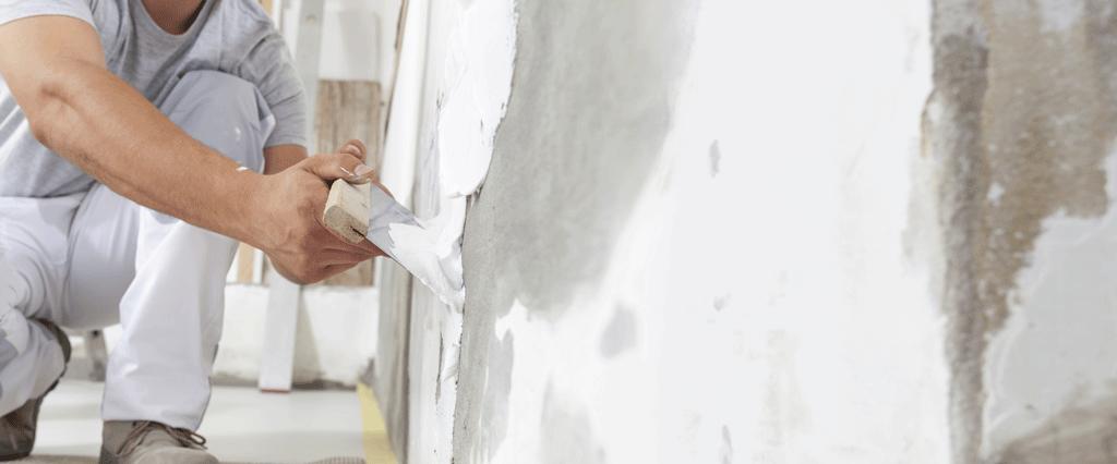 Operario colocando mortero antihumedad en una pared